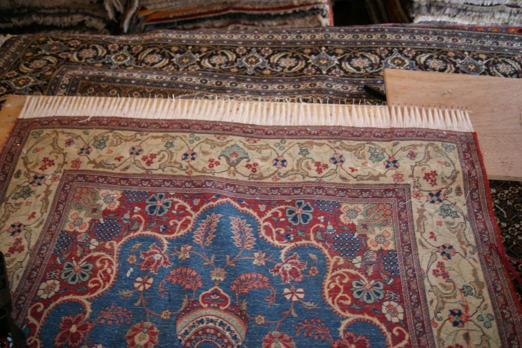 This image shows the rug in the process of the fringes being added. At this point, the rug is almost complete andneeds to be take off the loom and have its fringes trimmed.